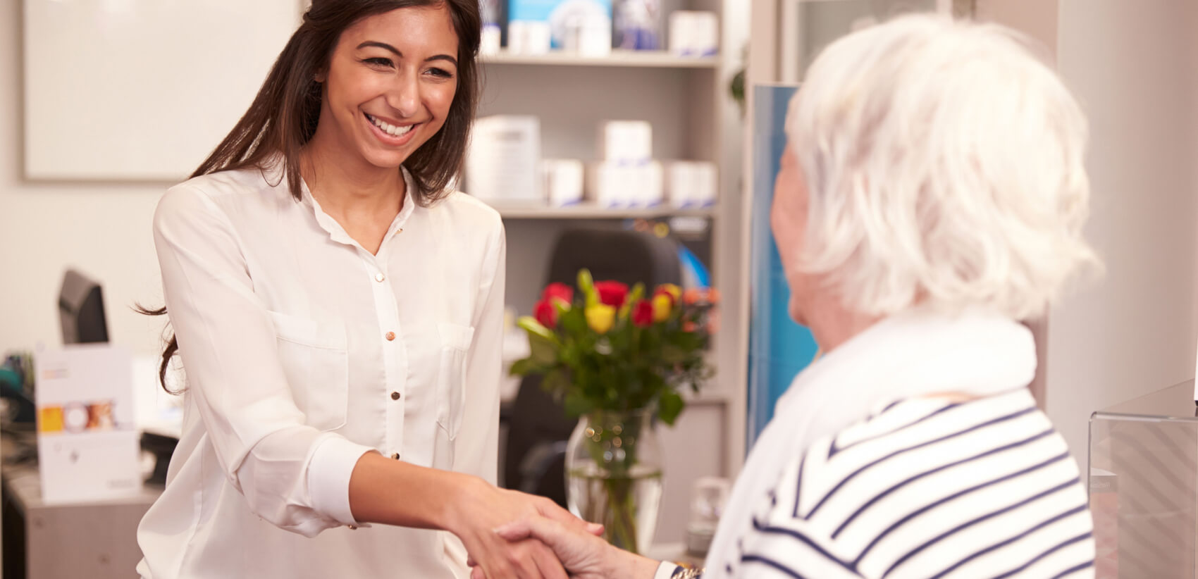 Healthcare management professional shaking hands with an elderly woman