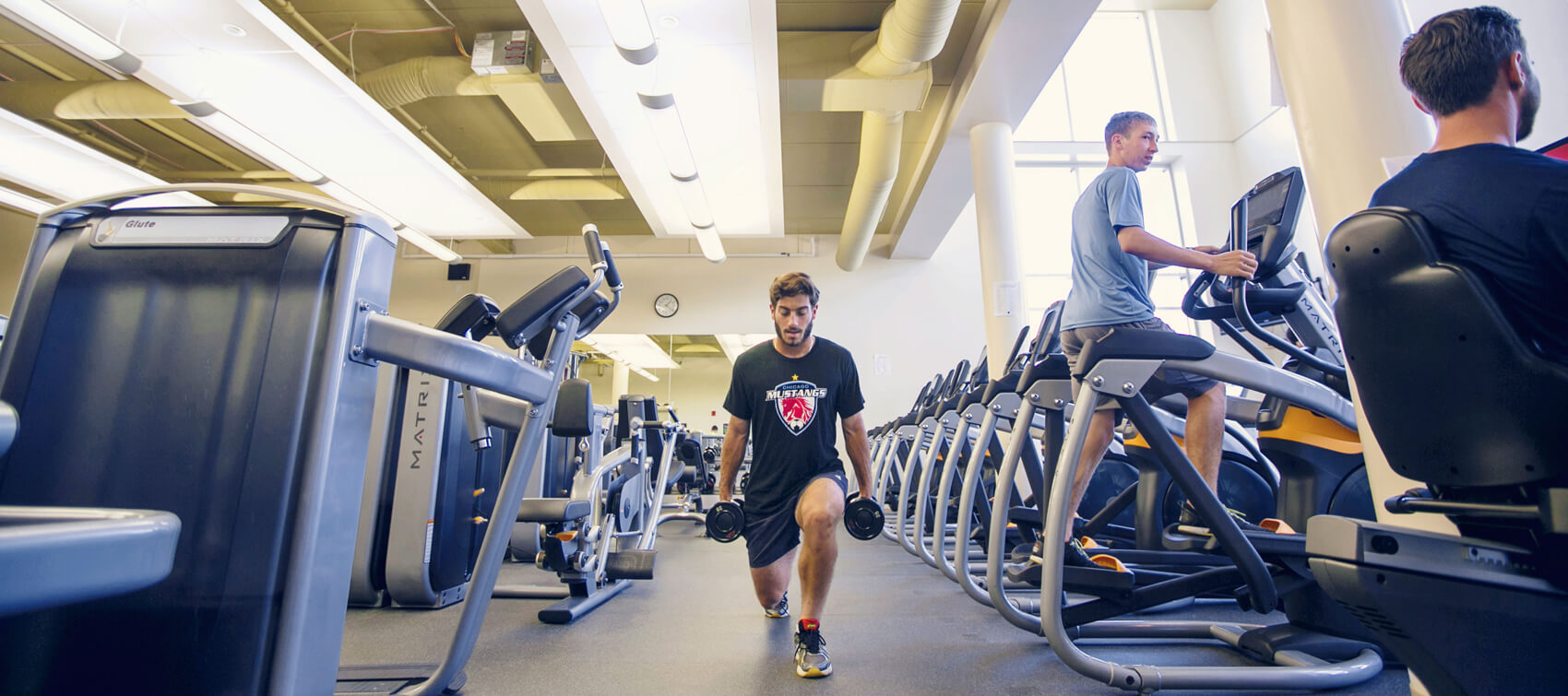 Man pursuing a fitness management degree exercising in a gym